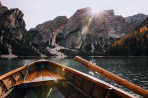 brown canoe in the body of water near mountain