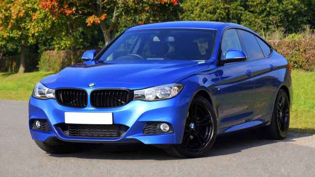 blue bmw sedan near green lawn grass